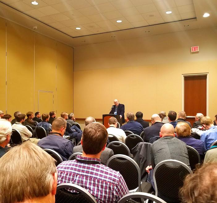 John Woodbridge addresses a packed room.