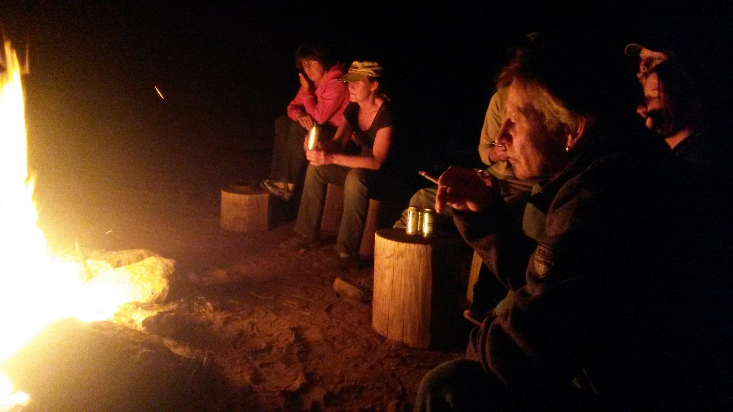At night we all sit around the campfire.  Abends sitzen wir alle am Lagerfeuer.