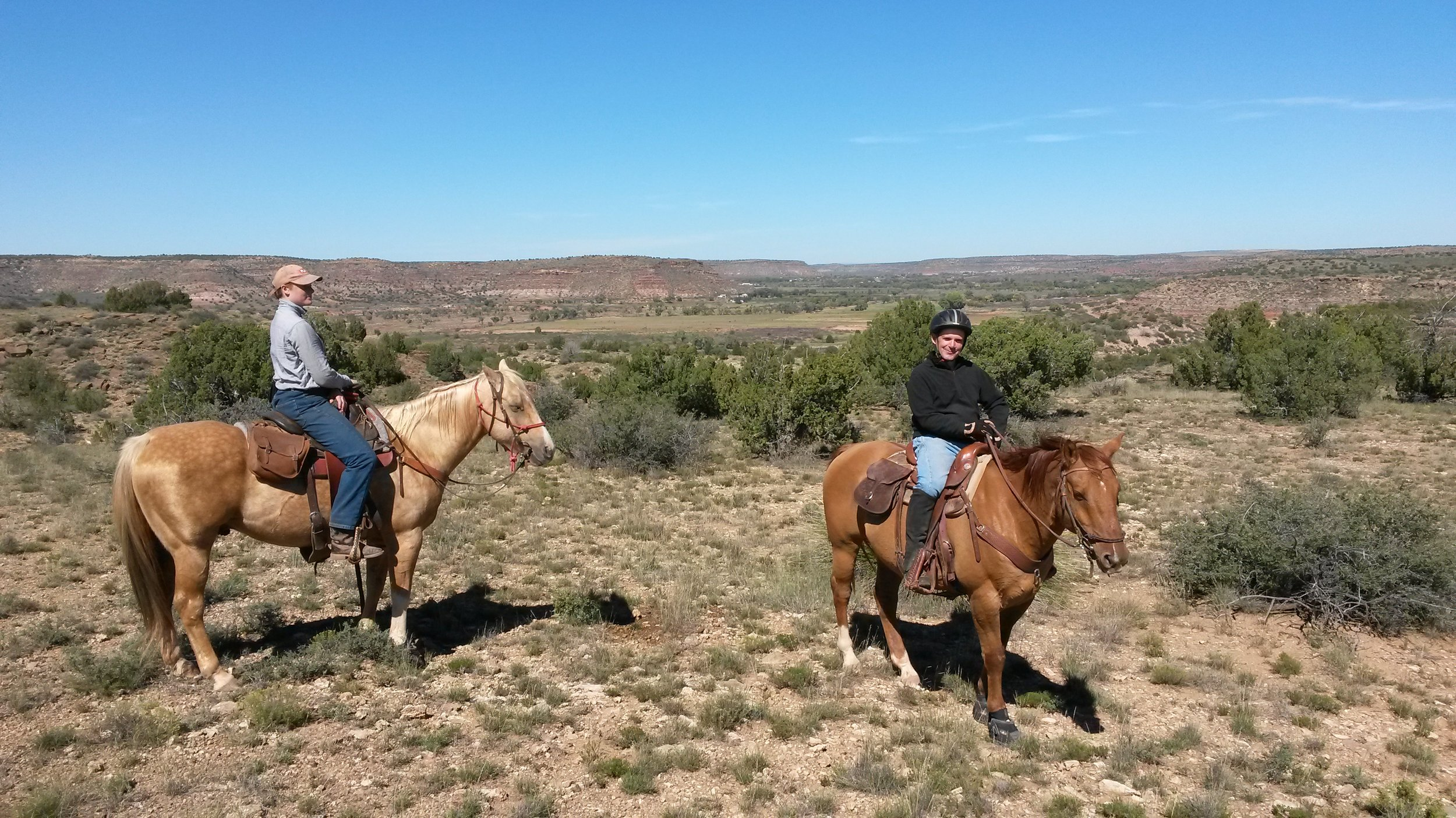 A trail ride in nice weather (left to right: Melanie on Johnny and Leo on Whiskey) with the Pecos Valley in the background.  Ein Trailritt in herrlichem Wetter (links nach rechts:Melanie auf Johnny und Leo auf Whiskey) mit dem Pecos Valley im Hintergrund.