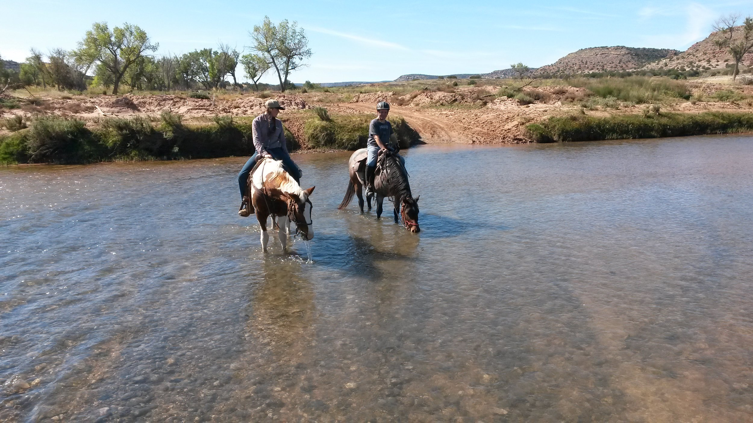 The infamous Pecos River - crystal-clear and well liked by our horses (left Melanie on Dolly, right Leo on Gus).  Der berühmt-berüchtigte Pecos River - kristallkar und sehr beliebt bei unseren Pferden (links Melanie auf Dolly, rechts Leo auf Gus).