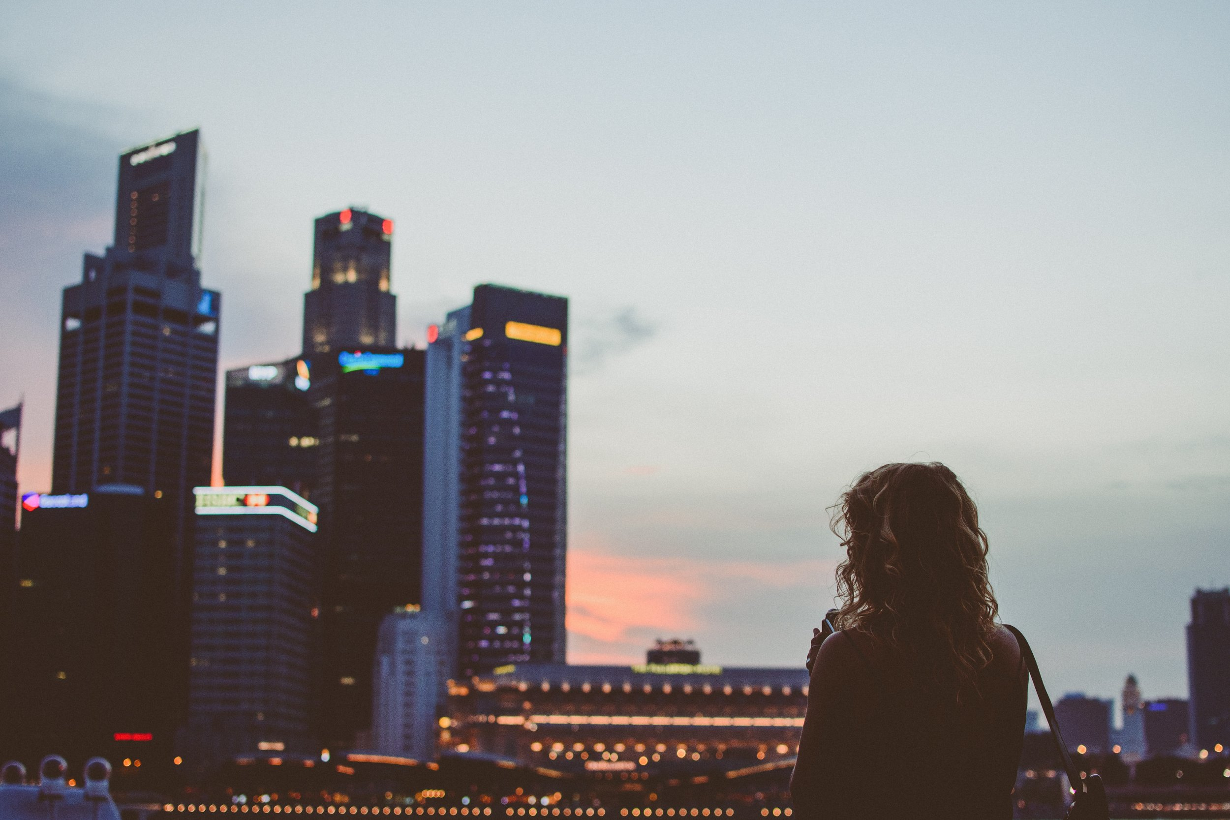 Girl looks over the Singapore skyline. Photo Credit: Andi Rizal.