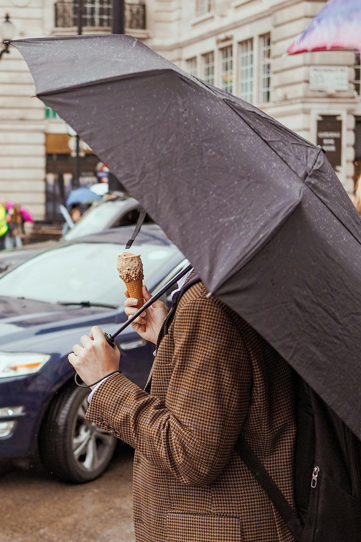 Man eating ice cream in the rain, London. Photo Credit: Josh Edgoose