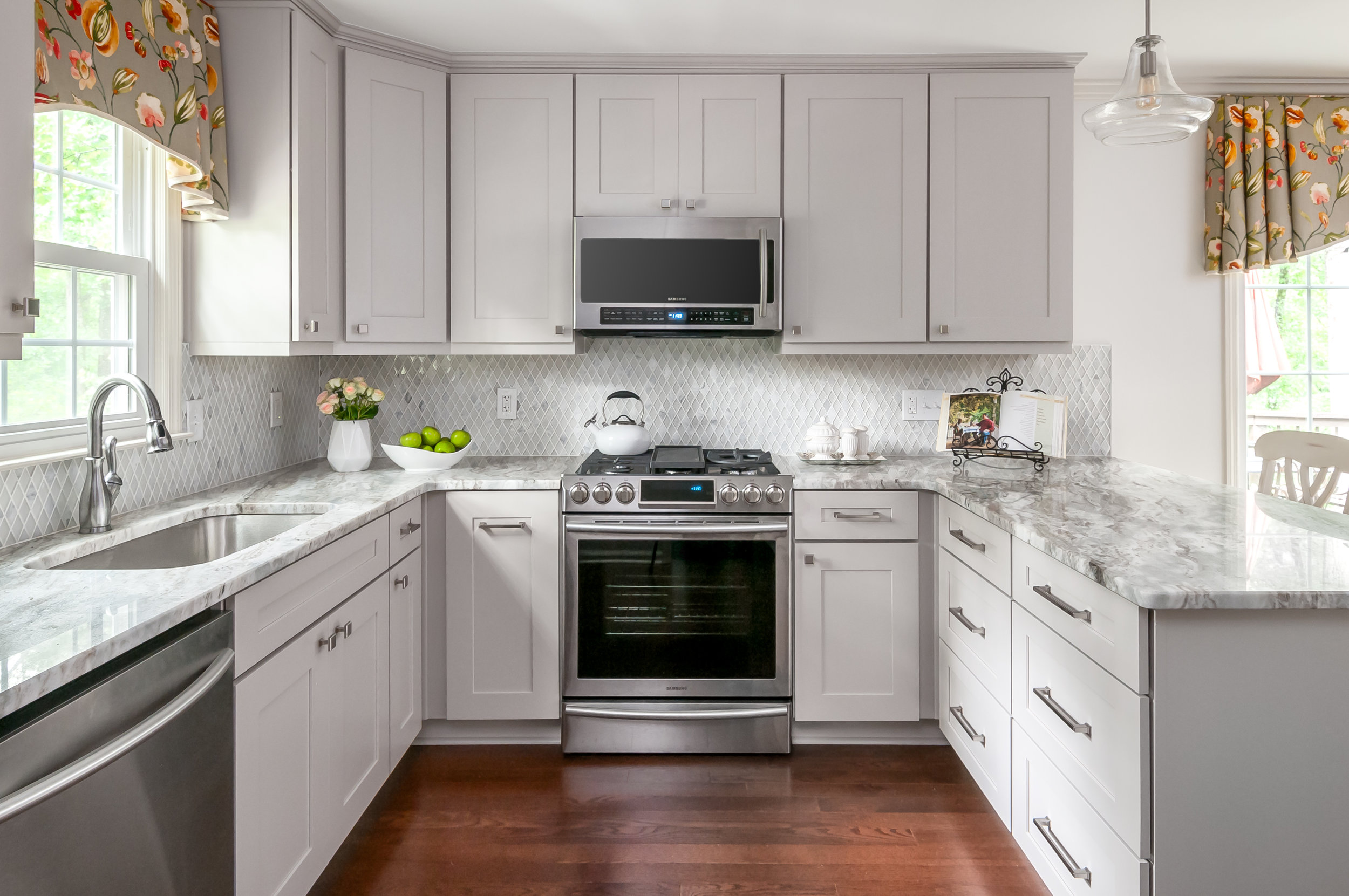New appliances and willow gray cabinetry create a clean feel to the heart of the kitchen. The hardwood floor from the adjoining family room was extended into the kitchen.