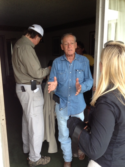 Texas Equusearch founder Tim Miller, center, in doorway of a West Baton Rouge motel room where Ronald Dunnagan attempted suicide in March, 2013
