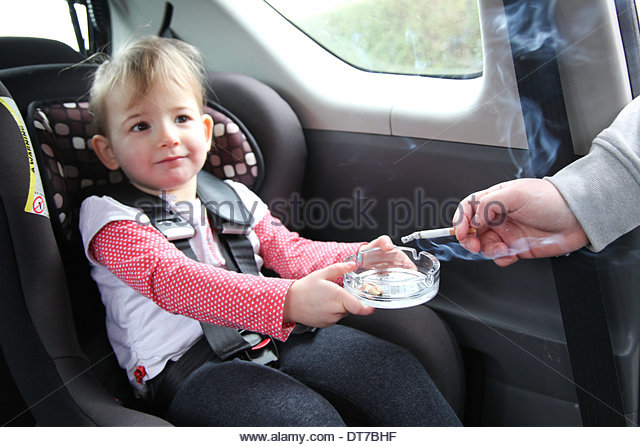 Child carrying ashtray for smoking parent. From alamy stock photos