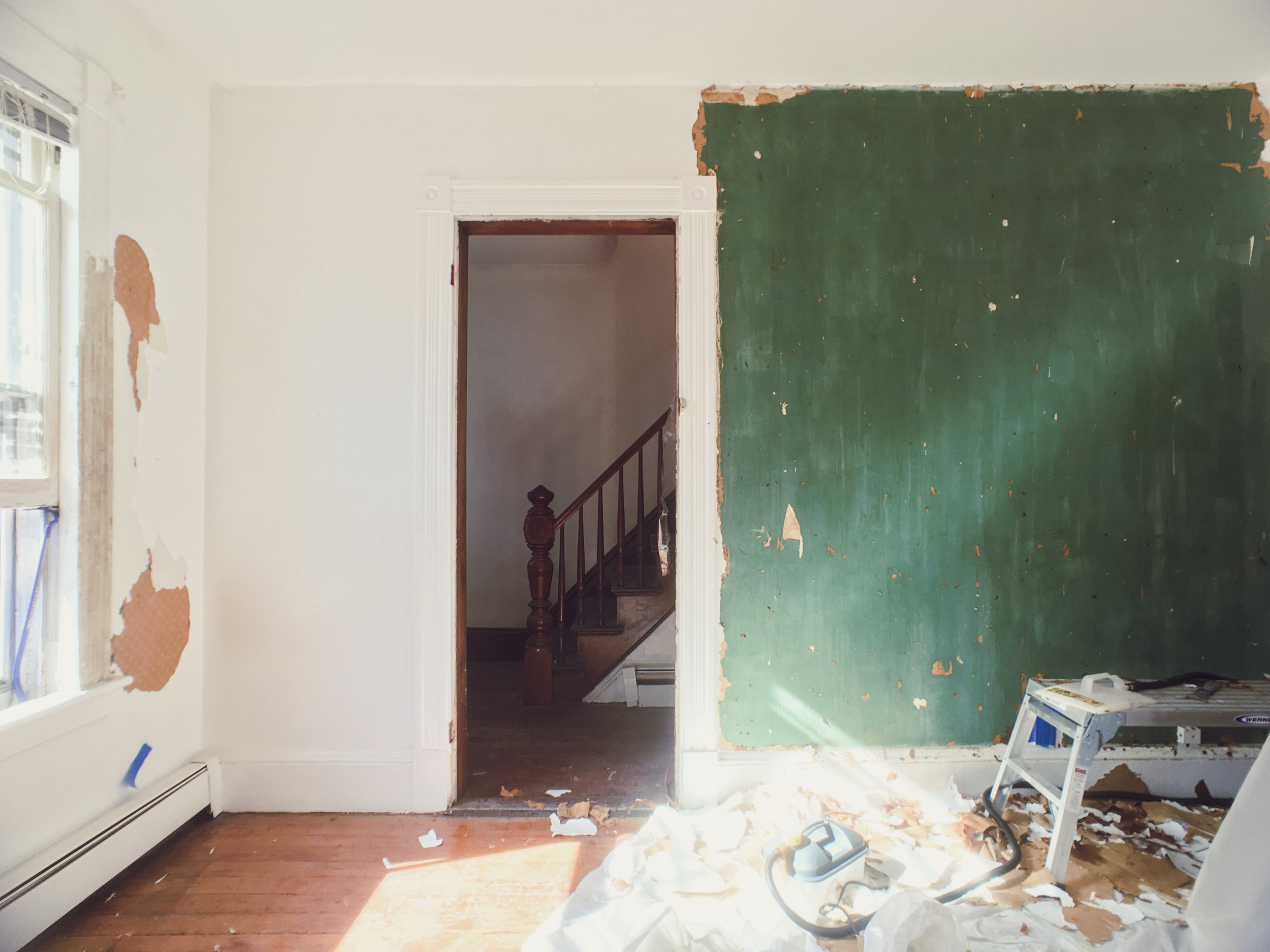 The first floor tenant apartment's original green plaster walls revealed after hours of stripping wallpaper.