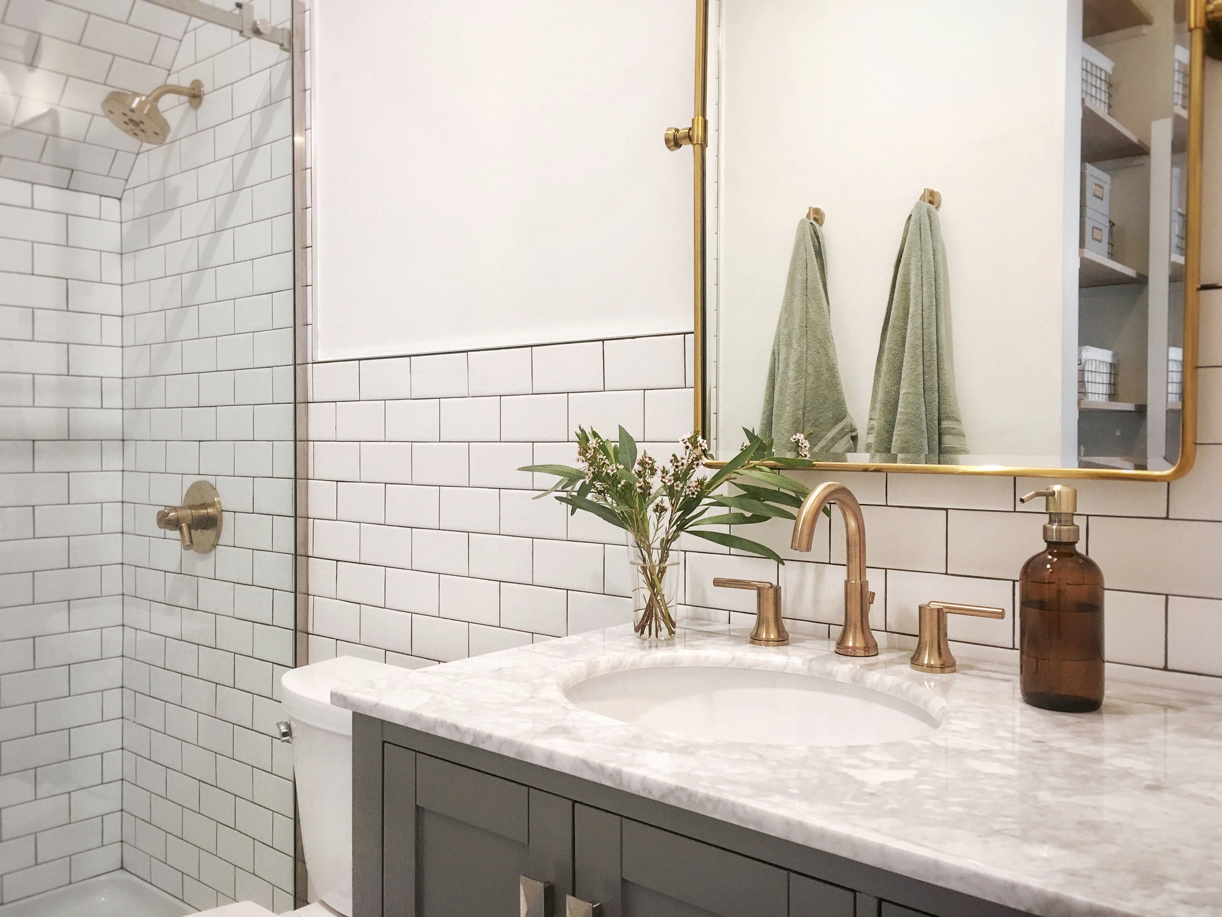 Lots of white tile, white marble, and brass fixtures brighten up the space and reinforce that vintage aesthetic.
