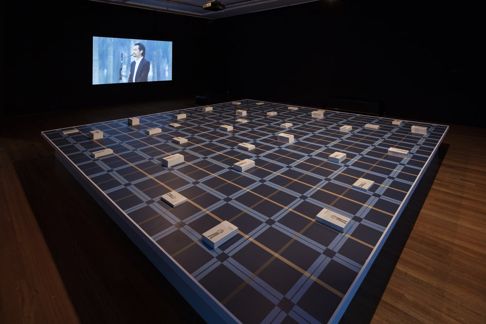 Yu-Cheng Chou,  A Working History Lu Chieh-Te , 2012. Installation, booklet (Chinese & English), 13 x 21 cm, 210 pages, pattern painted on wooden deck, 500 x 500 cm. Commissioned by Taipei Contemporary Centre in Taipei for the exhibition  Trading Futures , 2012. Commissioned by Te Tuhi in Auckland for the exhibition  Share/Cheat/Unite , 2016. Photo by Sam Hartnett