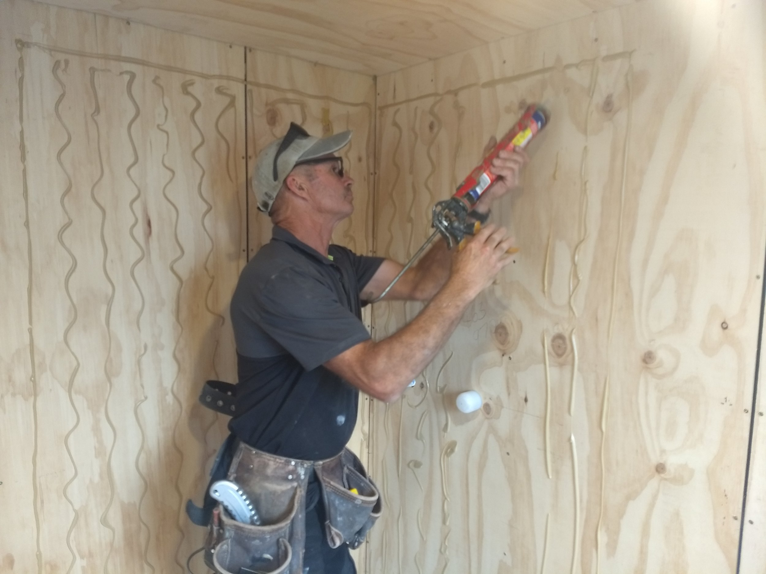 Grant attaches the acrylic shower lining.