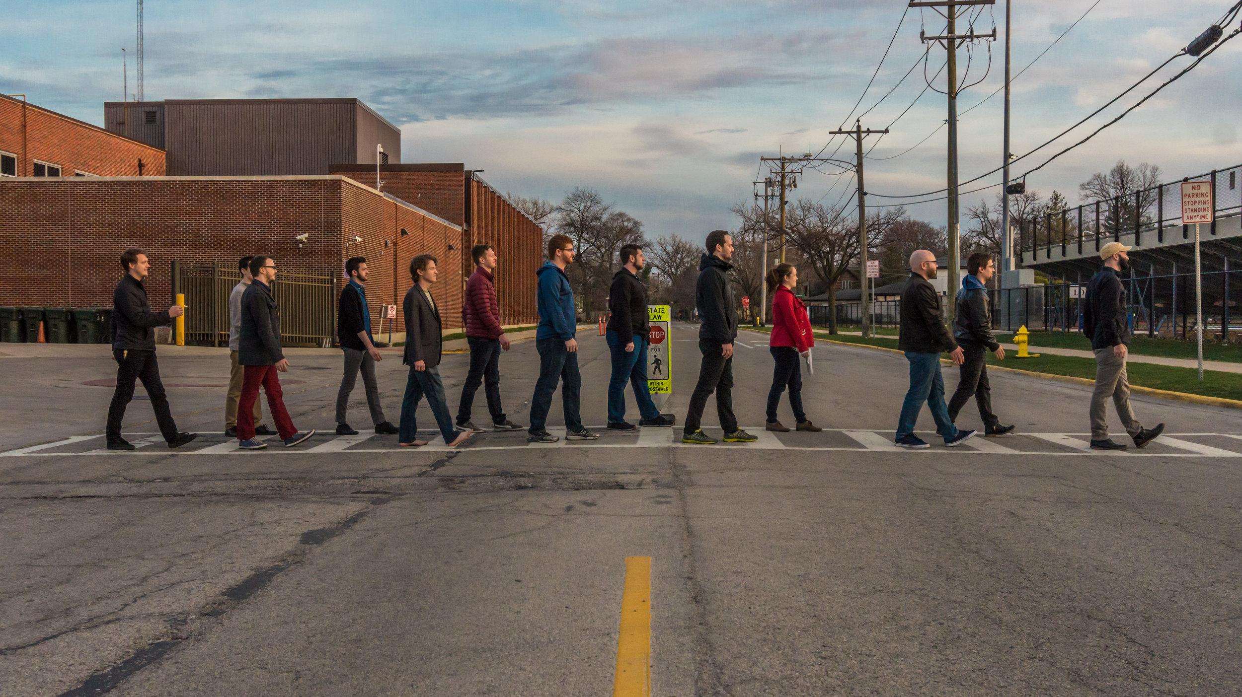 Members of the Heisenberg Uncertainty Players walking across a street (like Abbey Road)