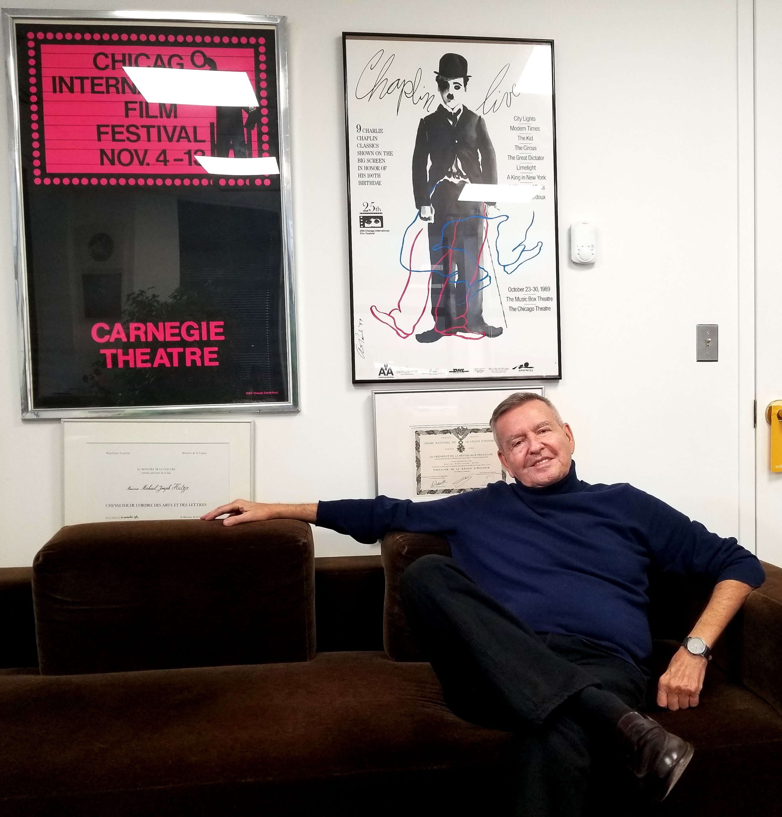 Chicago International Film Festival Founder/CEO Michael Kutza in his office. Above him to the left is the poster for the inaugural Chicago International Film Festival.