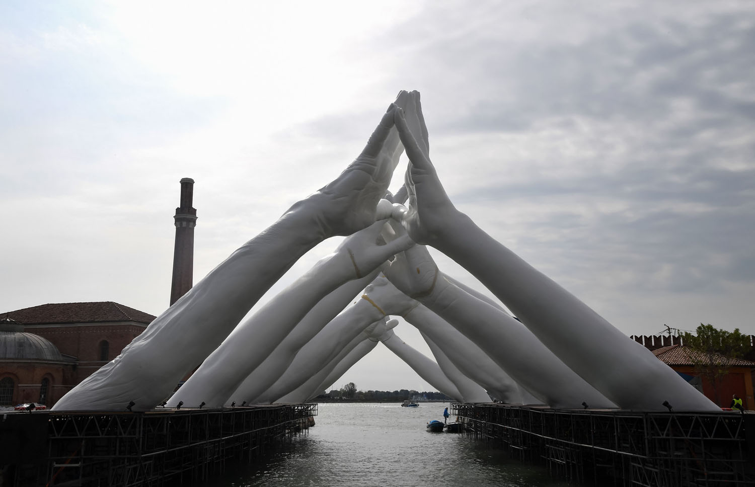 Italian artist Lorenzo Quinn's  Building Bridges , an installation showing six pairs of arching hands creating a bridge over a Venetian waterway in the Arsenal shipyard.