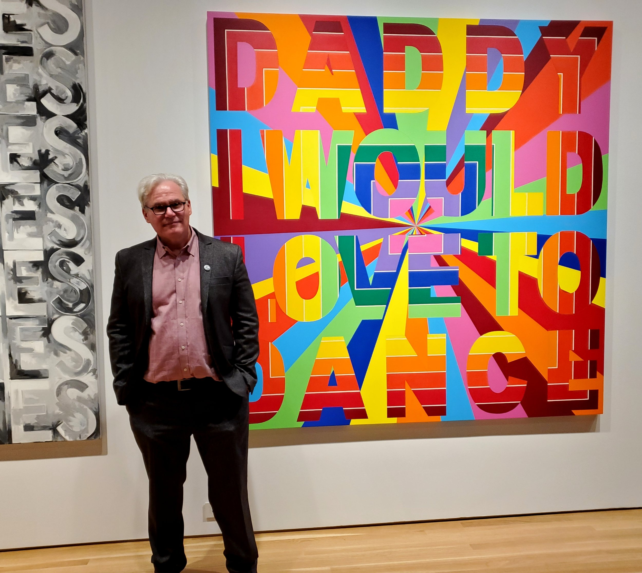 Curator Jonathan David Katz in front of DADDY I WOULD LOVE TO DANCE, Deborah Kass