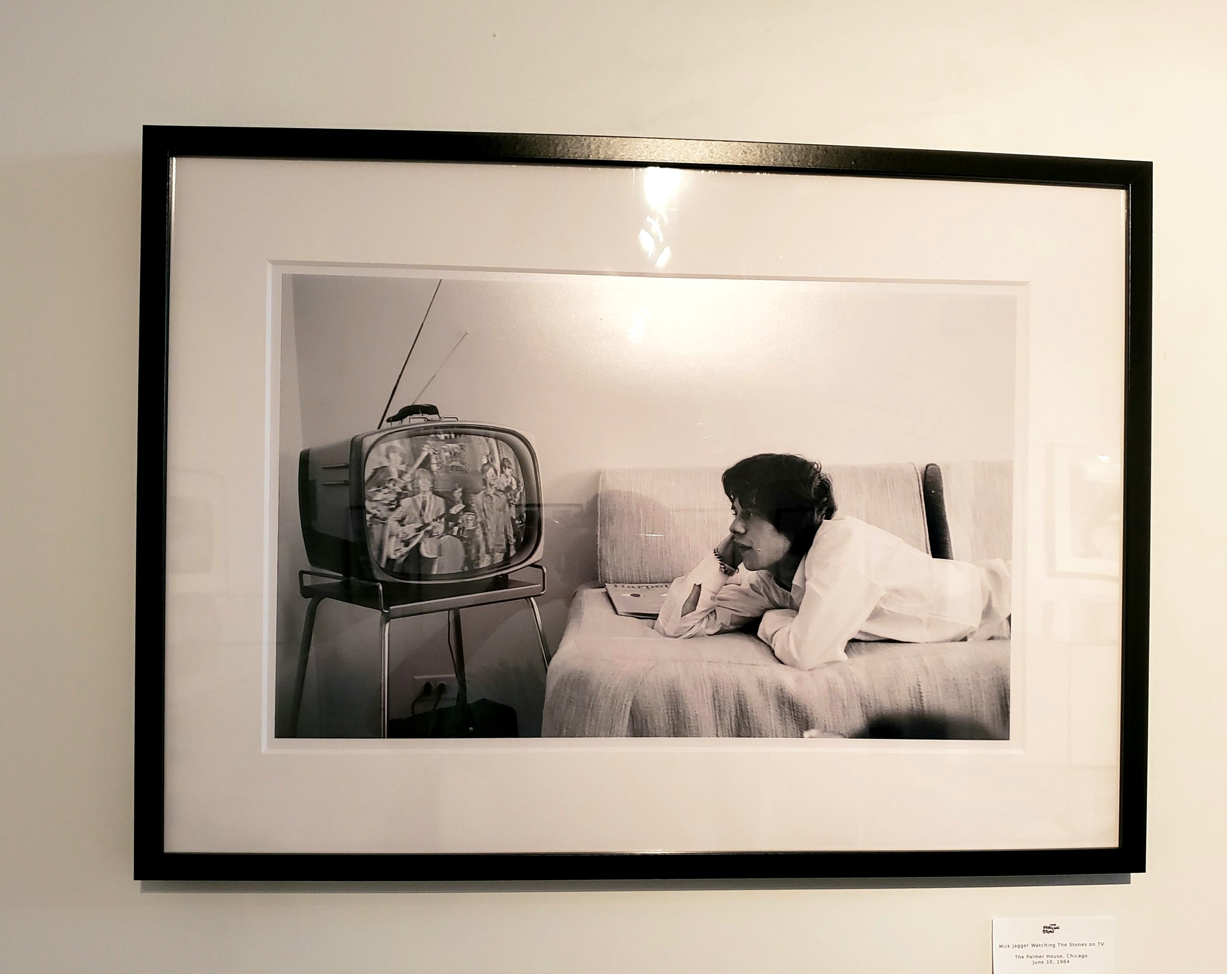 Photo of Mick Jagger watching himself on TV at the Palmer House Hotel in June 1964