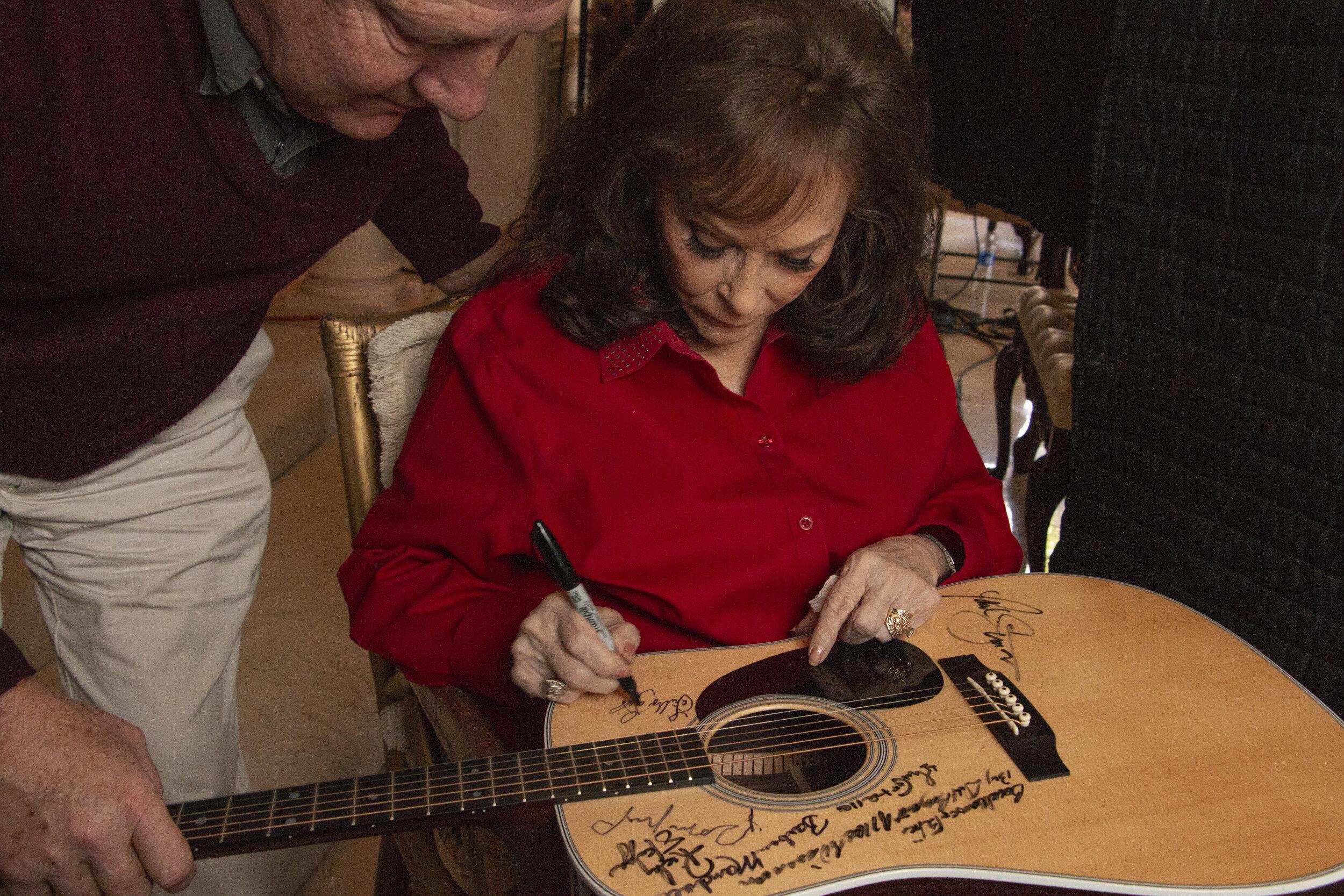Loretta Lynn signs Martin D-28 guitar