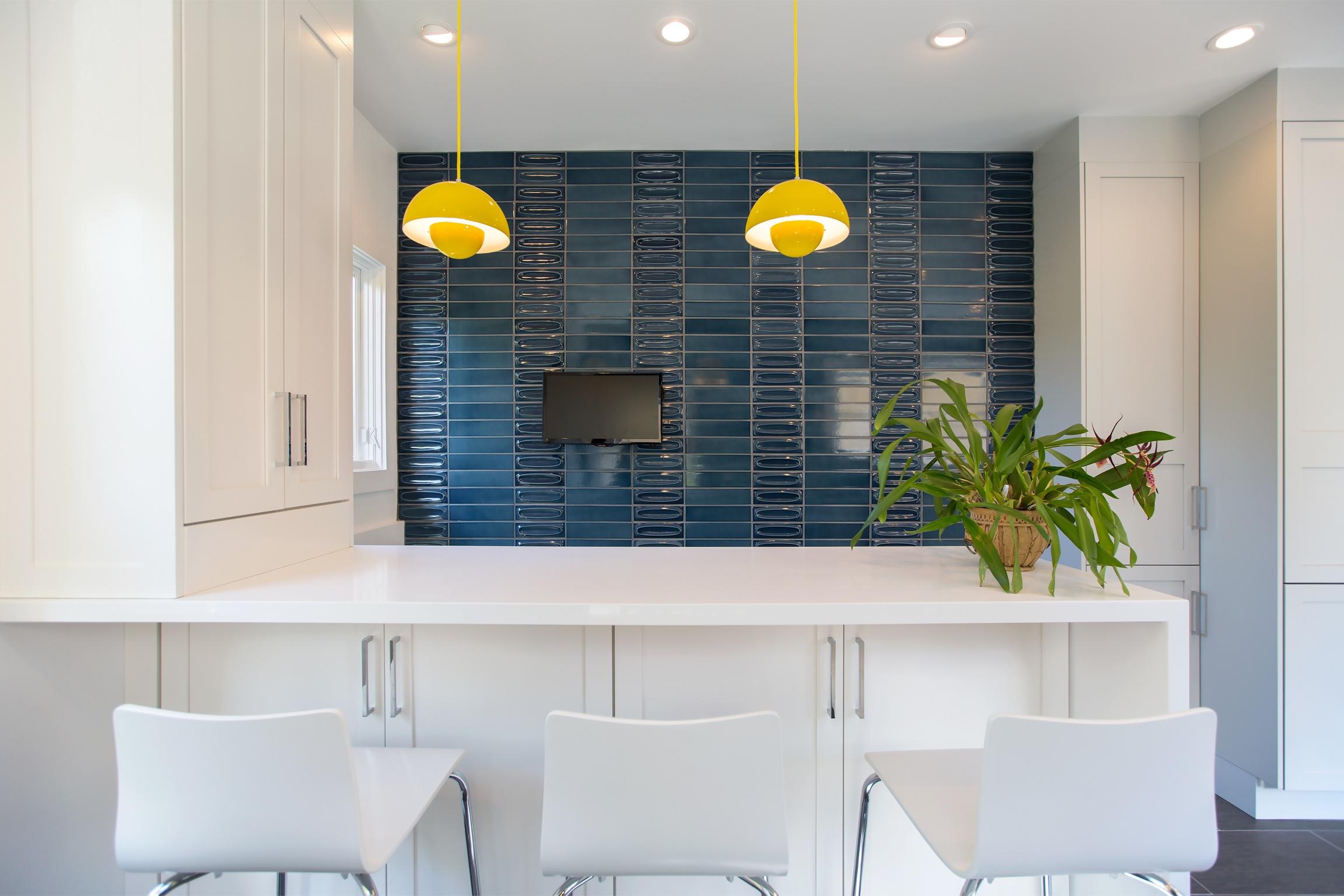 william-adams-design-christmas-tree-lane-2-kitchen-white-bar-seating-blue-tile-wall-yellow-lights.jpg