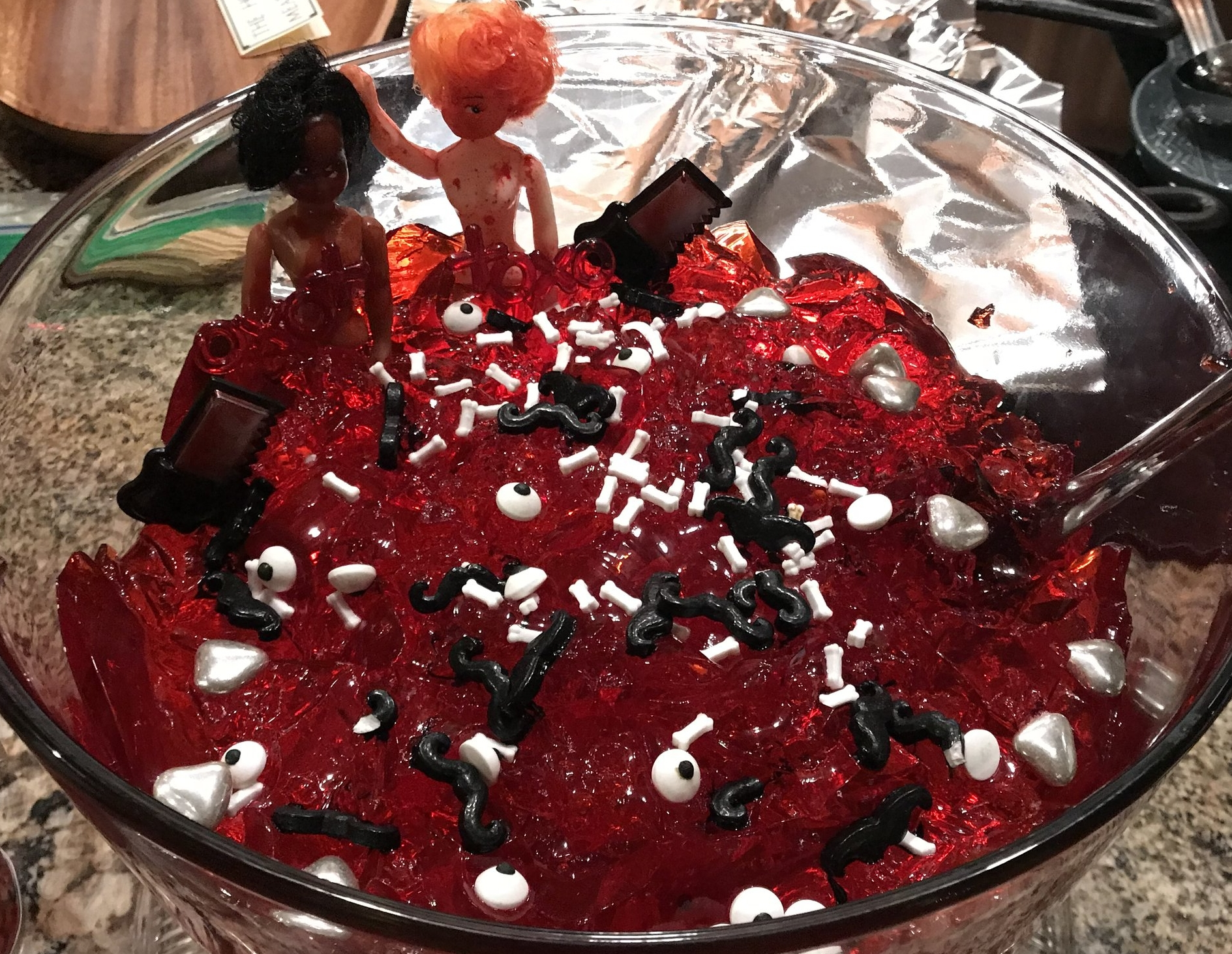mustaches, bones, eyeballs and silver hearts adorned the red gelatin.  Along with two bloody dolls and hand weapons.