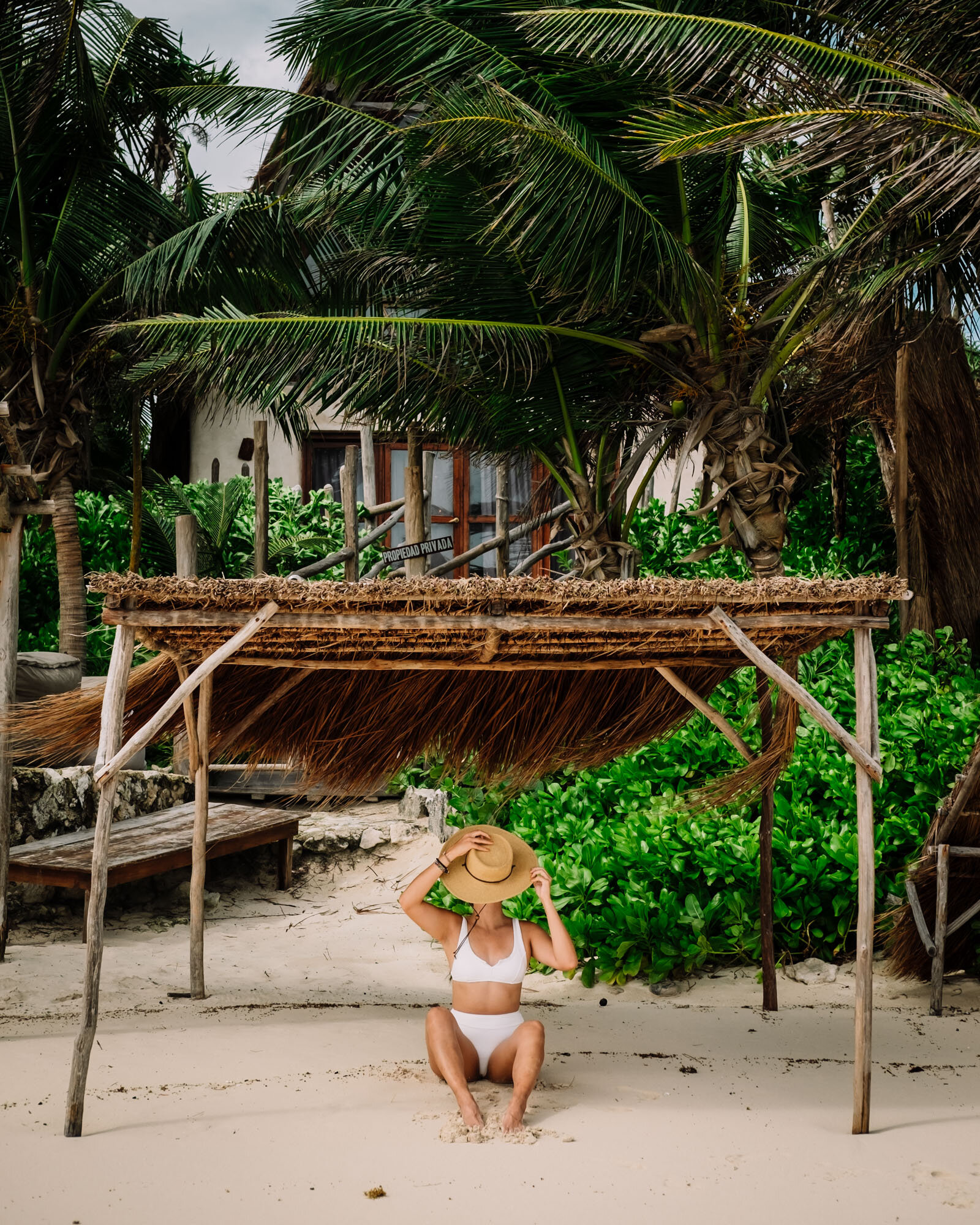 Rachel Off Duty: Woman in a White Swimsuit Sitting Under a Palapa in Tulum, Mexico