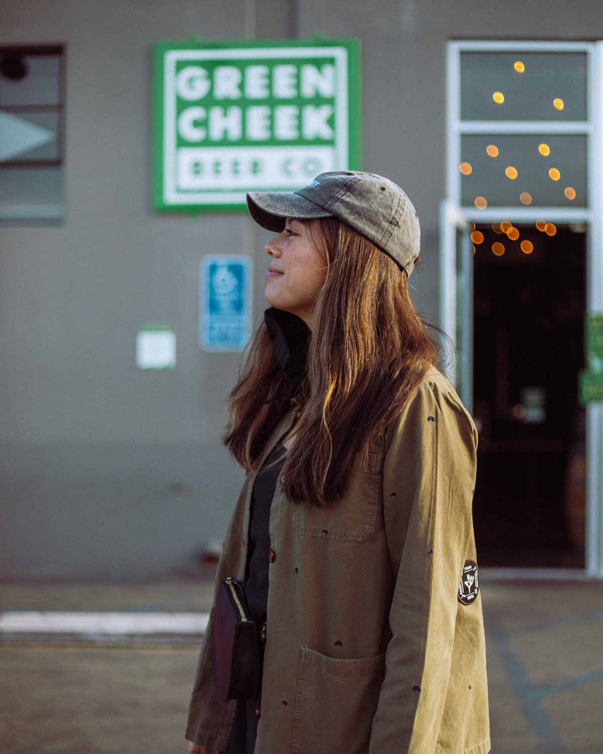 Rachel Off Duty: A Woman in a Green Jacket and Gray Hat Standing in Front of a Brewery
