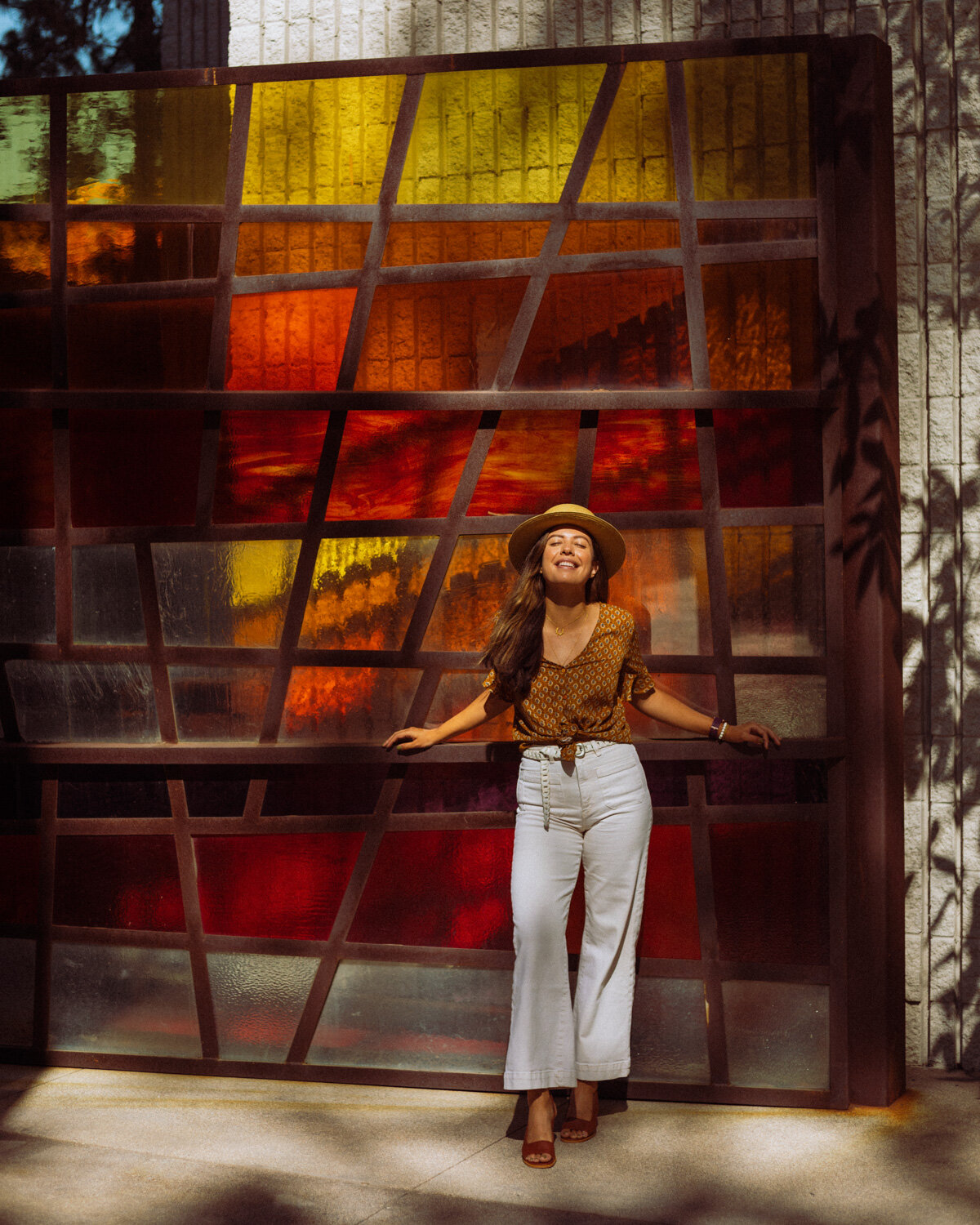 Rachel Off Duty: A Woman Smiling in Front of a Red, Orange, and Yellow Glass Art Piece