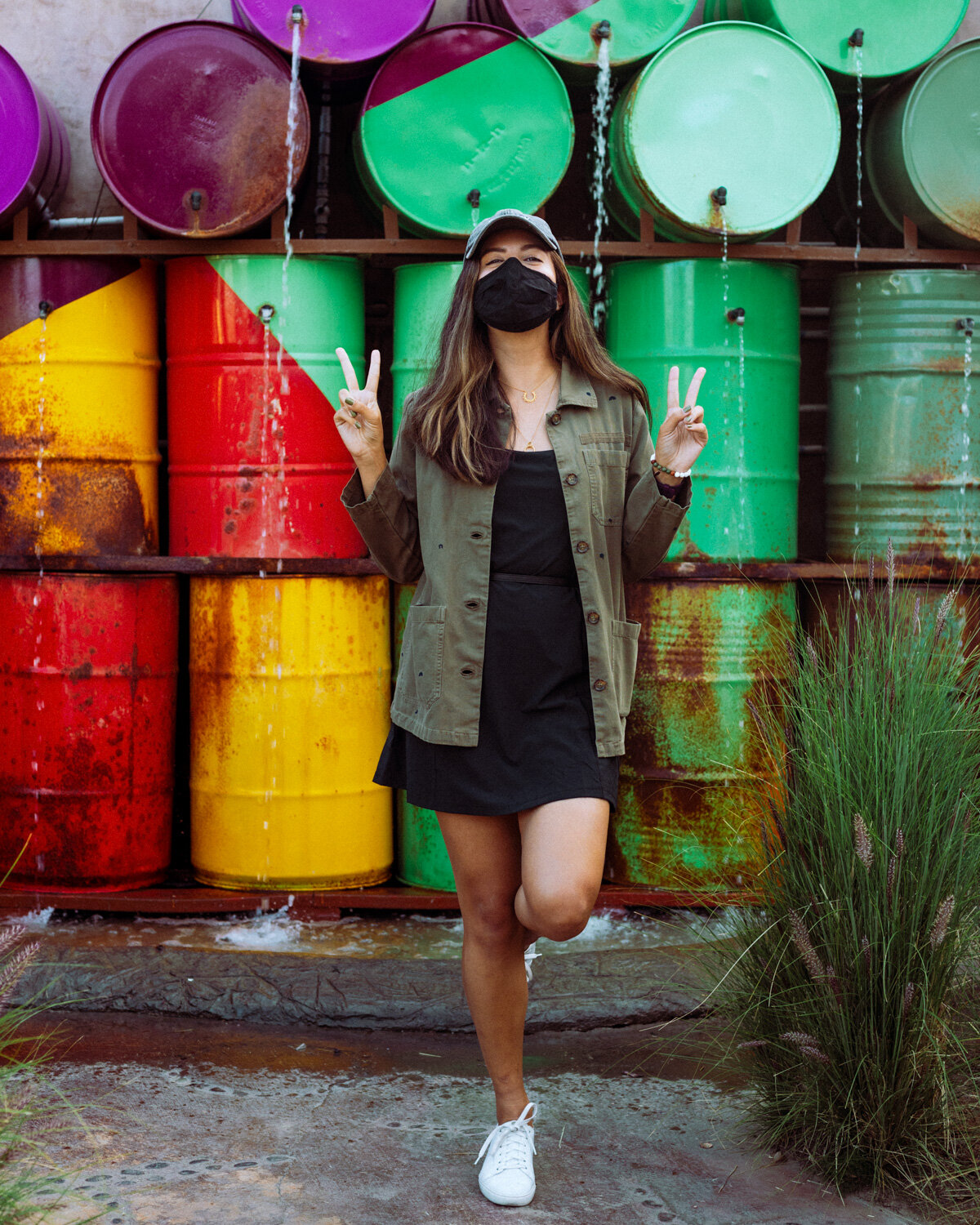 Rachel Off Duty: A Woman in a Black Dress and Black Mask Posing in Front of a Purple, Red, and Green Art Installation
