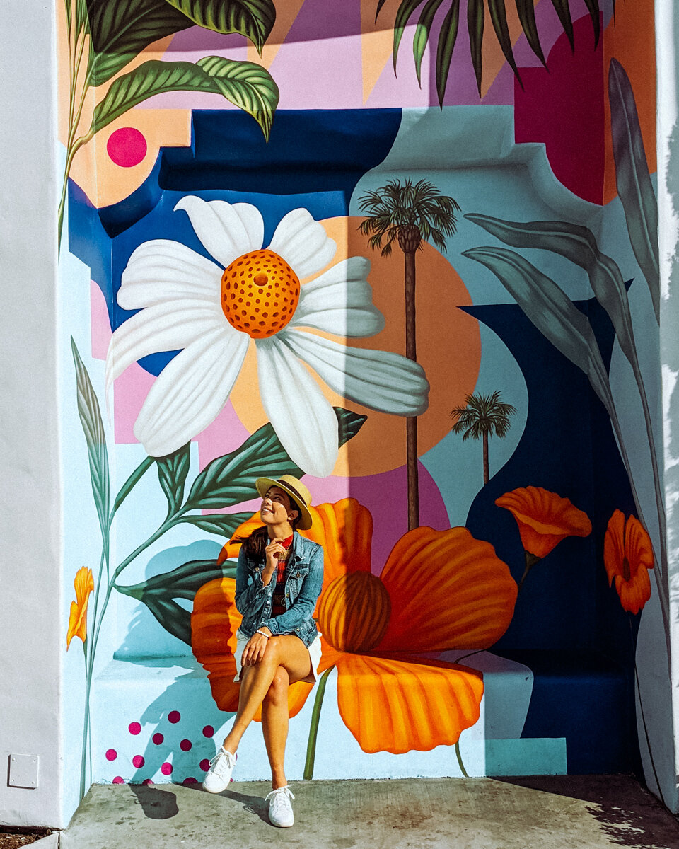 Rachel Off Duty: A Woman Sitting In Front of a Bright, Colorful Flower Mural