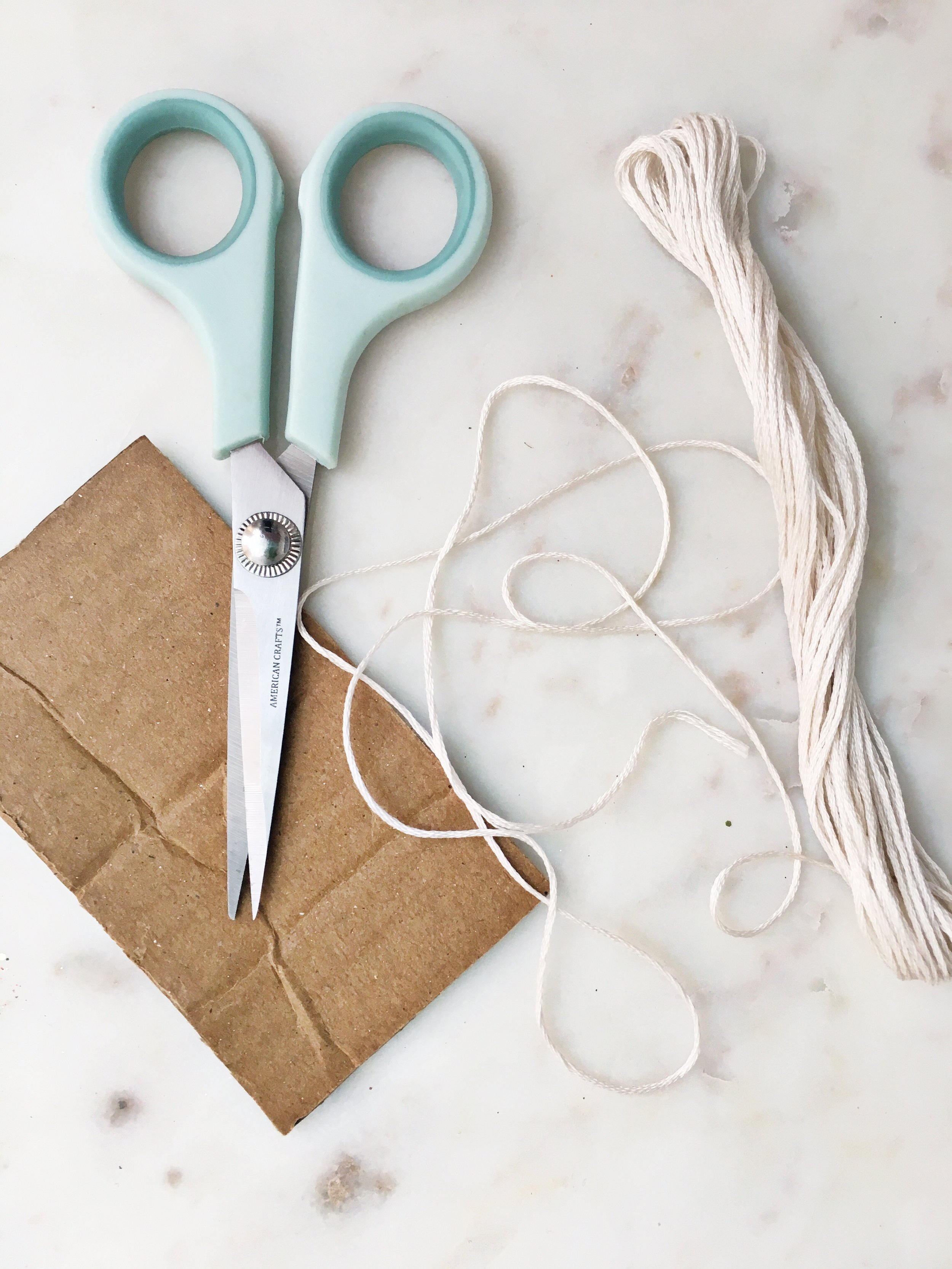 STEP THREE - To make the tassels you will wrap the embroidery thread around the scrap cardboard, cut to approx. 2