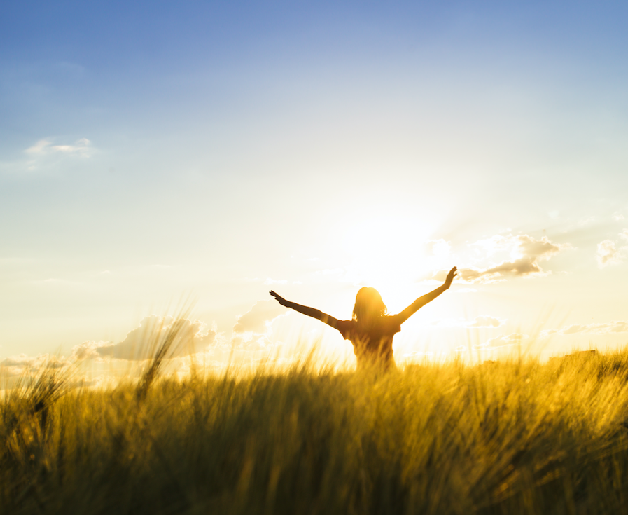 woman at sunrise in a field arms up.png