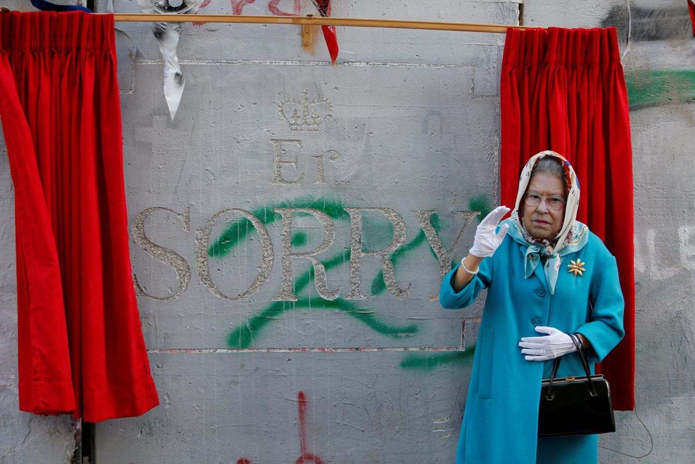 """Photo:British Street Artist Banksy unveils a satirical statue of Queen Elizabeth II during his """"apologetic street party"""" in Bethlehem, Reuters.  Photo Courtesy: PA Images"""