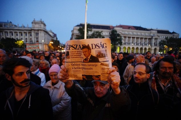 A man holds up the last printed edition of Nepszabadsag during a demonstration organized to express solidarity with the Hungarian political daily Nepszabadsag in Budapest, Hungary, Oct. 8, 2016.  Photo Courtesy: VOA News