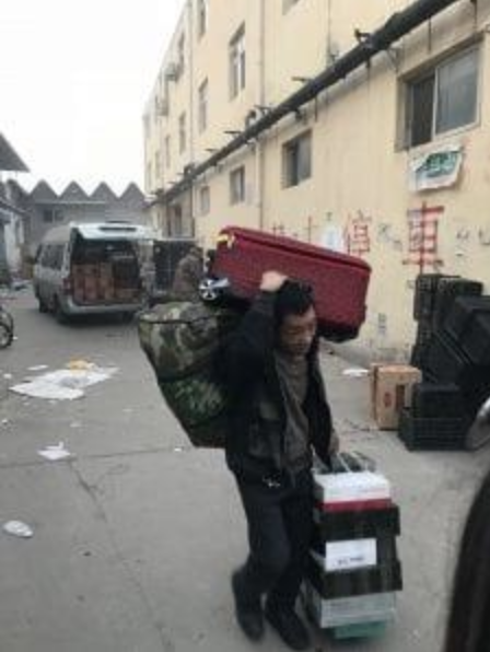 A migrant worker carries his belongings after being evicted from his home in the Daxing district of Beijing, on Saturday.  Source: Luna Lin/The Washington Post