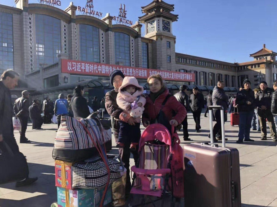 """A migrant family is leaving Beijing under the eviction. They had 15 minutes to clear all their belongings. Behind them is a big banner saying the great """"Xi Jinping new era.""""  Source: Twitter @QiZHAI"""