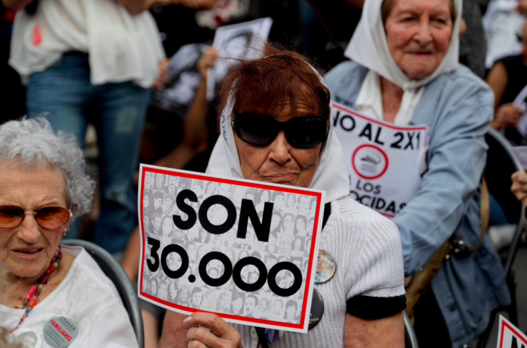 "Hundreds gathered outside the courtroom, listening to the verdicts for the accused shown on a screen outside. One holds up a sign that reads in Spanish ""they are 30,000,"" referring to those killed by the Argentine dictatorship (Washington Post)"