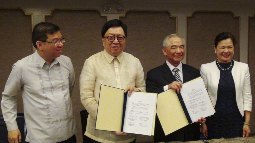 Representatives of Taiwan (right) and the Philippines (left) show the signed deal. (Source: Central News Agency)