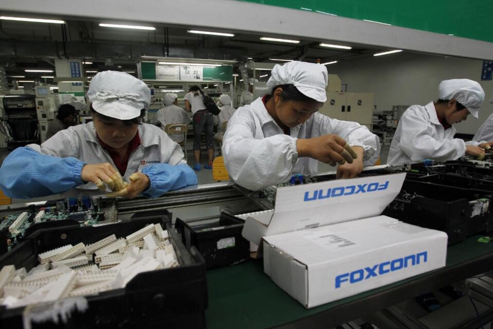 Foxconn workers working in assembly lines inside the factories. (Source: Kin Cheung/AP Photo)