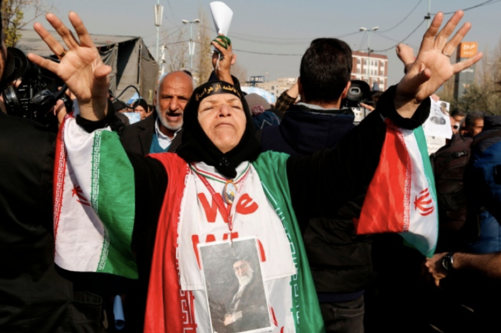 A woman on January 5 shown wearing a picture of Supreme leader Ayatollah Ali Khamenei at a state-sponsored rally, which have taken place as counter protests to show government support  Source: Atta Kenare/AFP/Getty Images