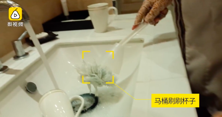 A cleaning lady is washing a cup by a toilet brush. (Source: Pear Video)