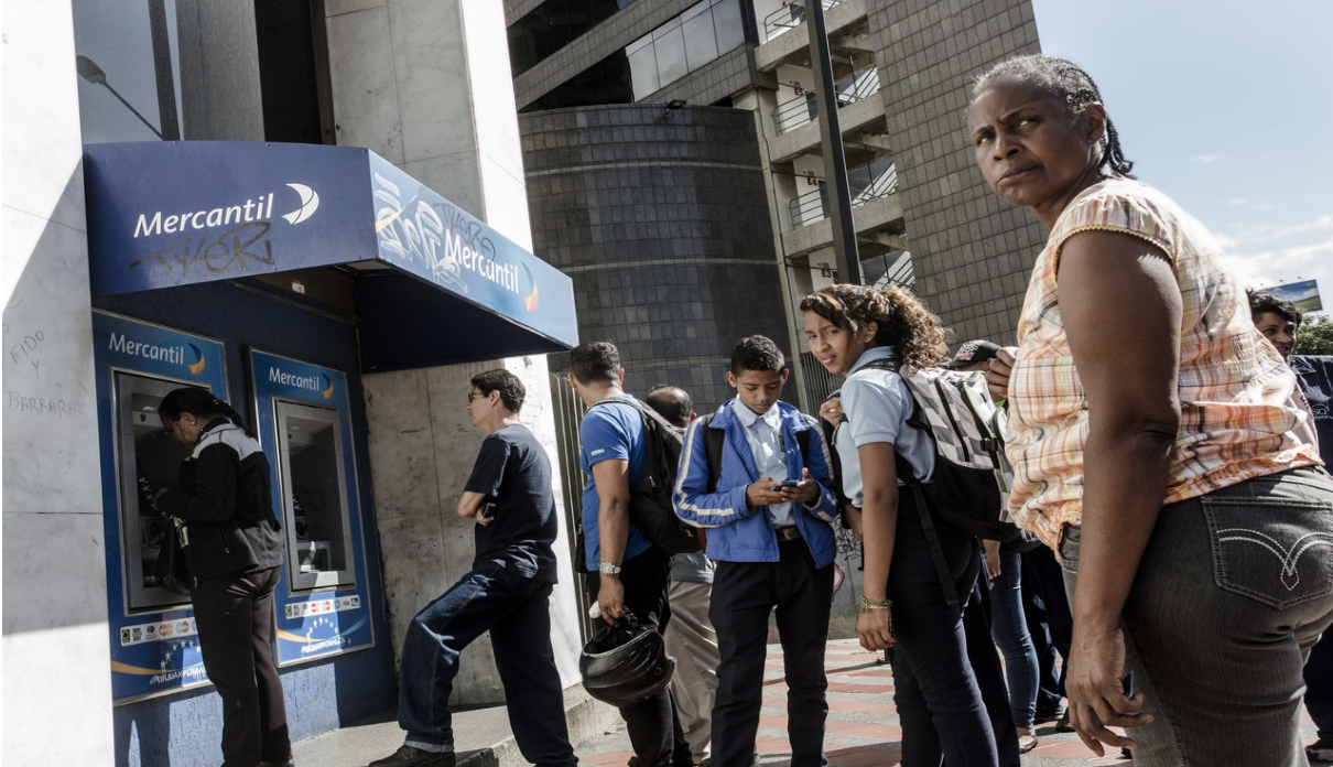 Photo: Venezuelans stand in line to withdraw cash from an ATM at the height of the cash crisis.  Source: The Wall Street Journal