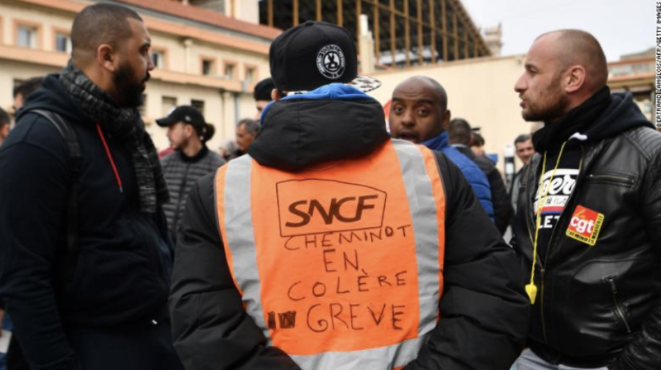 """CNN : A man wearing a jacket reading, """"angry railway worker on strike"""" at Marseille train station"""