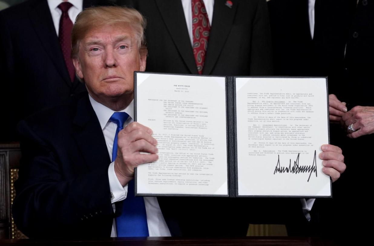 President Trump showing the executive memorandum on imposing new tariffs against China   Source: Reuters