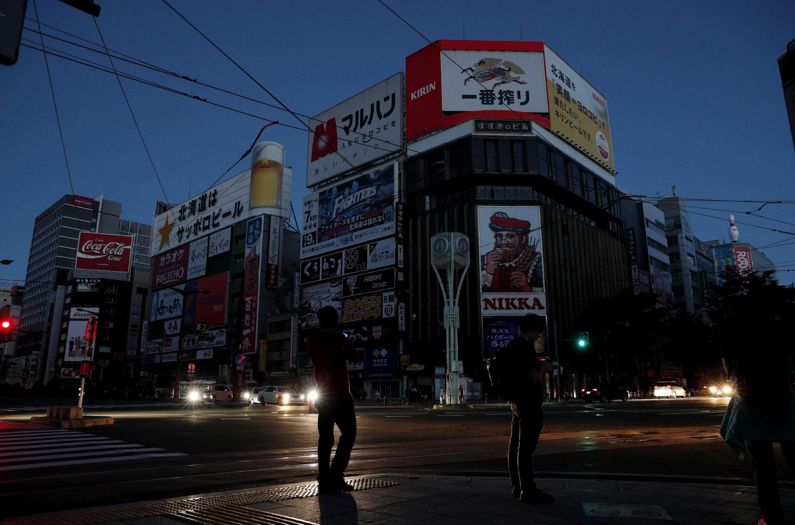 [Photo: The usually-bright neon lights of the advertisements on the buildings in Sapporo City's Susukino entertainment district were darkened on the night of Sept. 6 as Hokkaido faced an island-wide blackout. Photo:  Kyodo ]