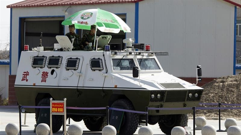 [A paramilitary People's Armed Police armored personnel carrier stands guard at Hotan Airport. Photo:  AP Photo/Ng Han Guan ]