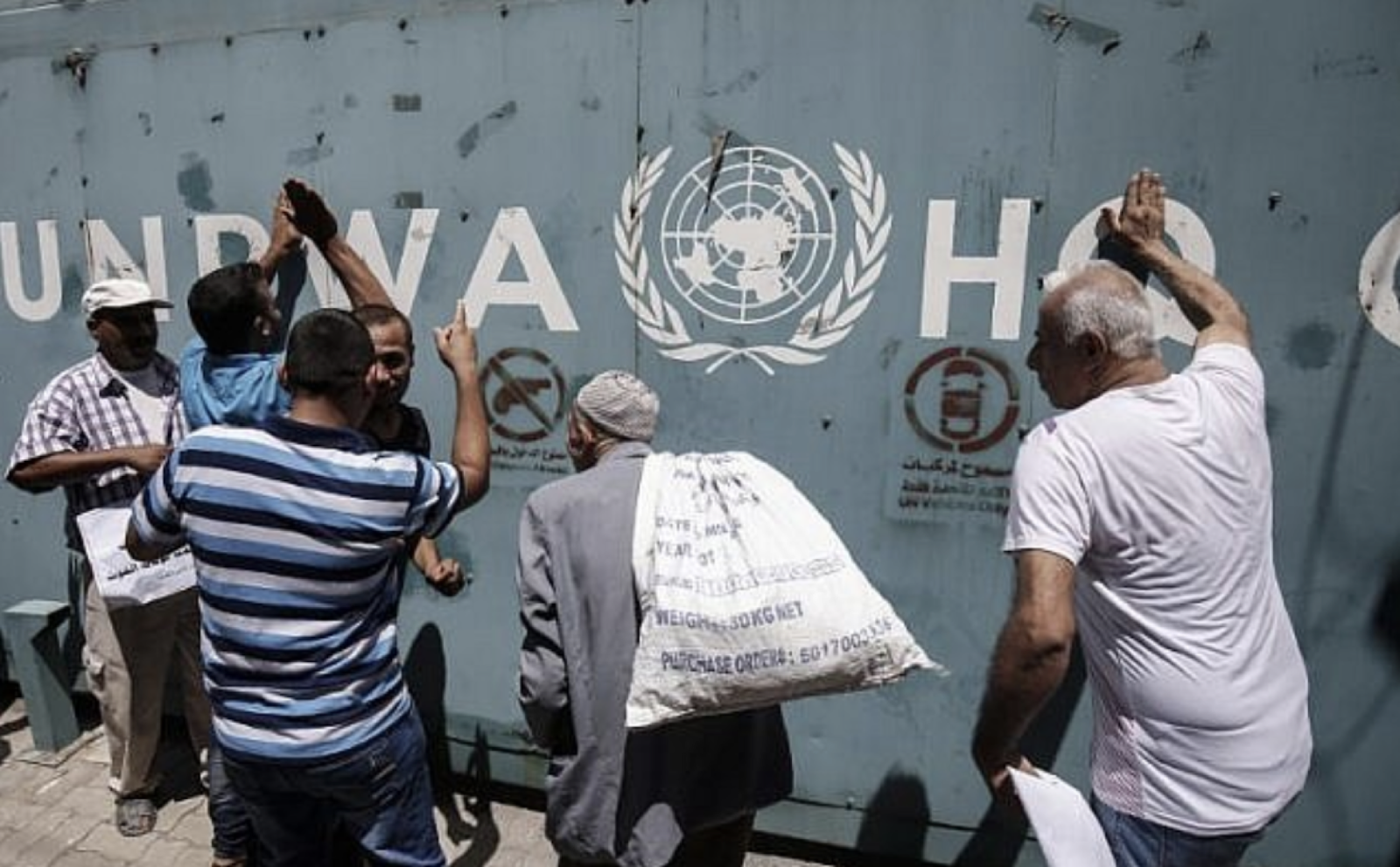 [Photo: UNRWA employees and their families protest job cuts announced by the agency outside Gaza City in July 2018. Source:  AFP/Said Khatib ]