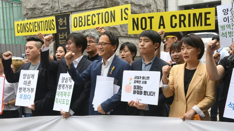 [Photo: Activists and conscientious objectors to mandatory military service rally outside of the Constitutional Court of Korea in Seoul on June 28, 2018. Source:  CNN ]