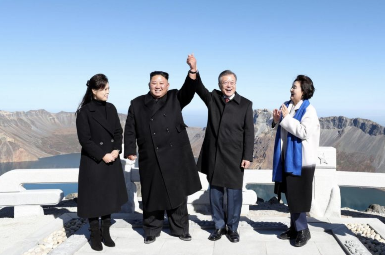 DPRK Chairman Kim Jong-un (second from left) and ROK President Moon Jae-in (second from right) raise their joined hands as Ri Sol-ju (first from left) — wife of Chairman Kim — and Kim Jung-sook (first from right) — wife of ROK President Moon — look on at the summit of Mount Baekdu in the DPRK on Sept. 20, 2018. (Photo:  Reuters