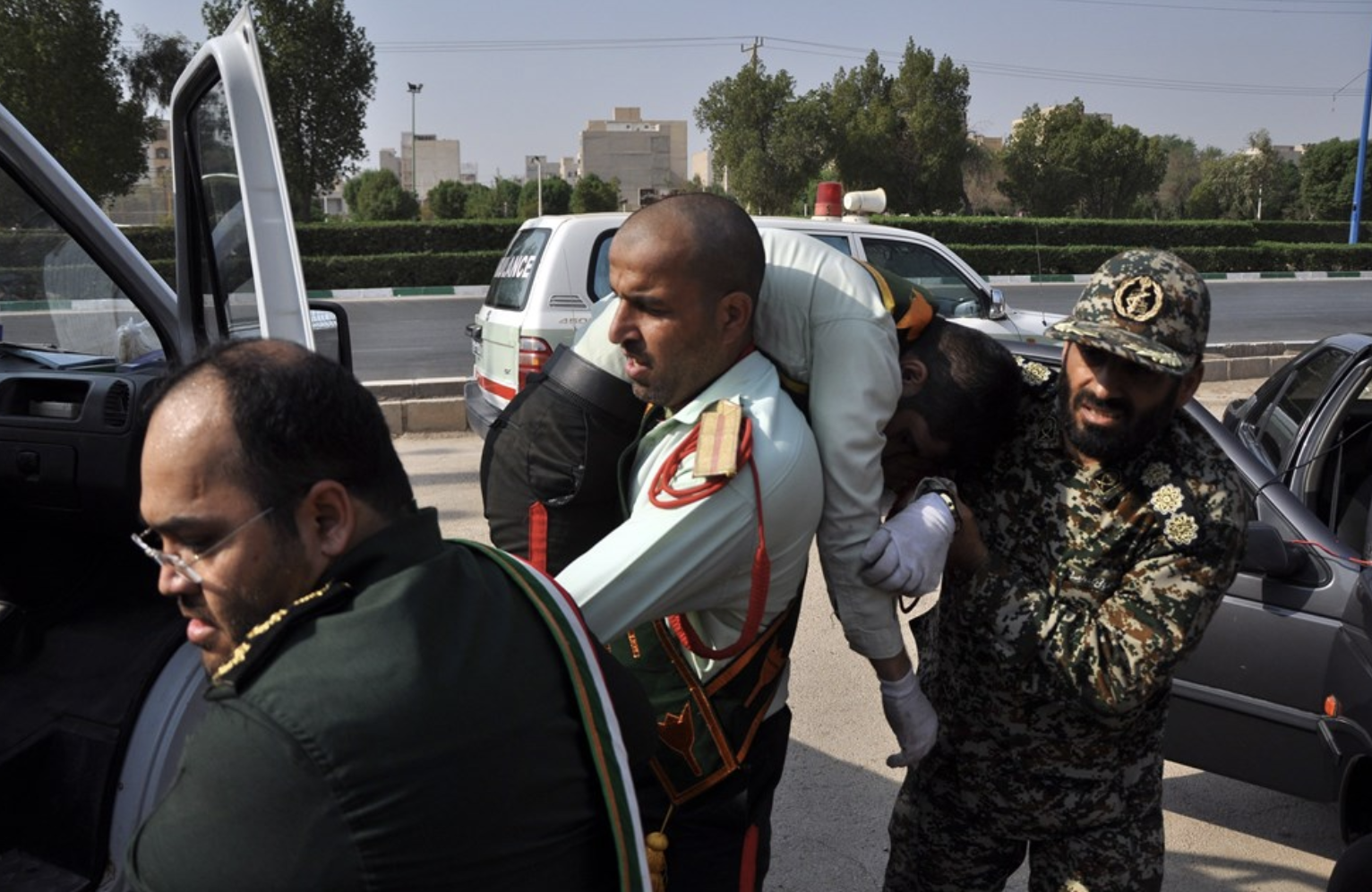 An injured member of the Iranian Revolutionary Guard is carried to get medical attention after Saturday's attack on a military parade in Iran.  Photo : Behrad Ghasemi/EPA