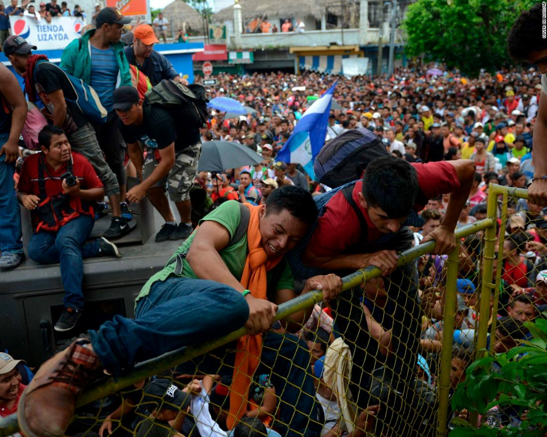 Honduran migrants rush the border fence in an attempt to cross into Mexico on Friday.  Photo: CNN .