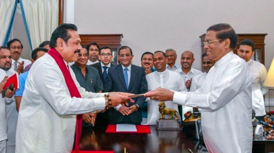 President Sirisena (right) handing materials to former president Rajapaksa (left) on October 26, 2018; Photo:  Los Angeles Times