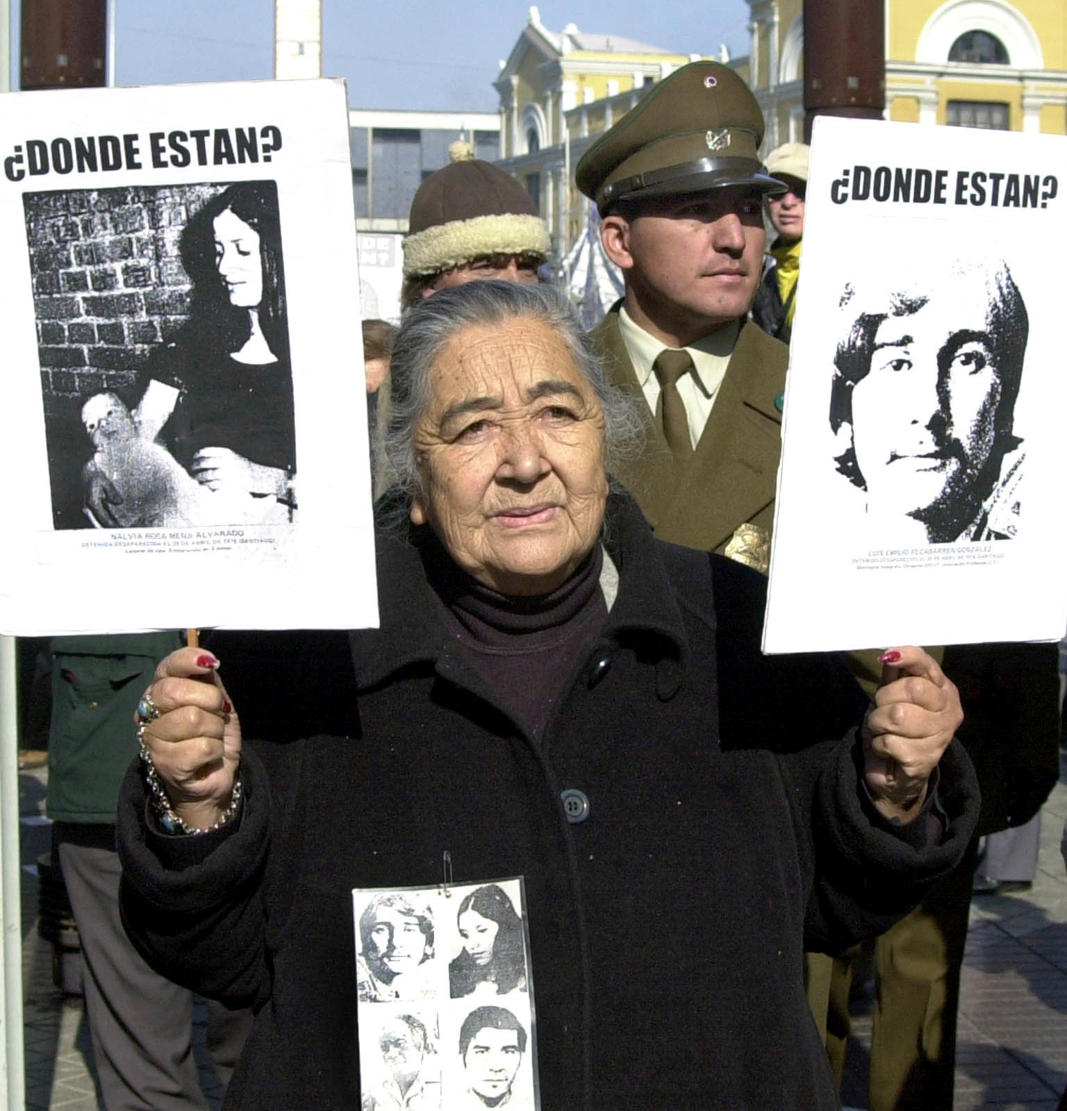 Ana González at a 2002 protest with pictures of her missing family members  Photo:  Santiago Llanquin/Associated Press via CBC