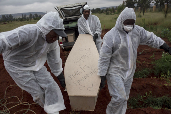 Mortuary workers bring an unidentified man in a coffin to a cemetary outside of Johannesburg. Photo: Bram Janssen/ AP Photo .